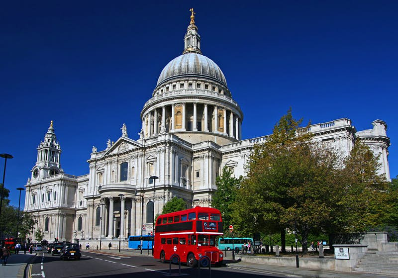 A red double-decker bus rolls past the white-washed, stone, domed St. Paul's Cathedral; Heathrow layover