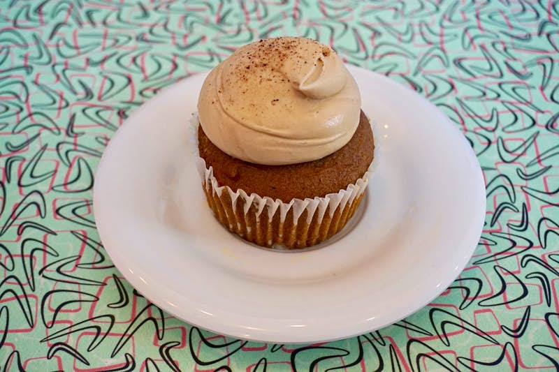 A cupcake with a generous swirl of icing sits on a white plate; underneath is a light blue tablecloth with a pink and black abstract pattern.