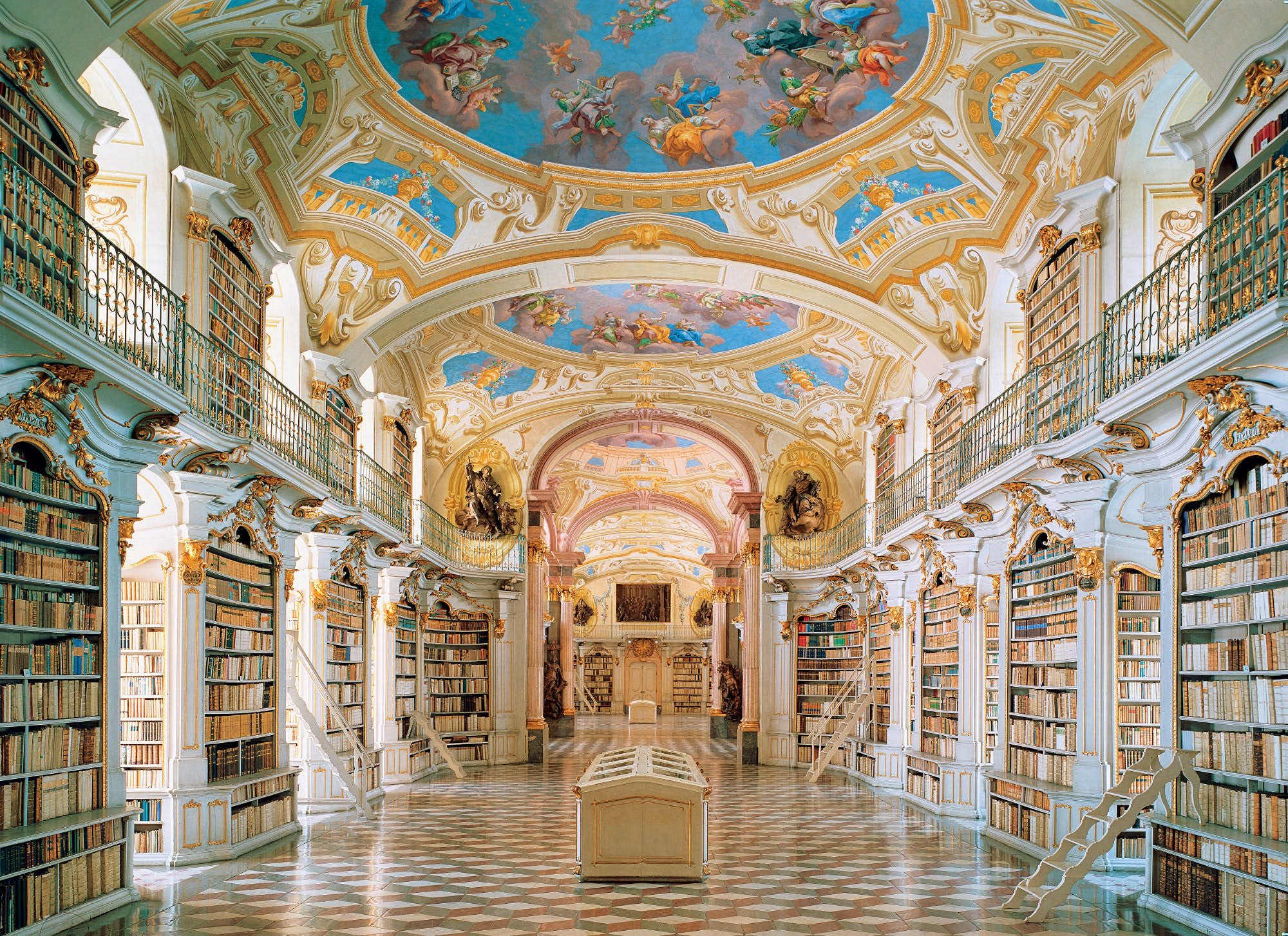 A long hall is supported by rectangular pillars that double as bookcases, each edged with white and gilt baroque columns. A balcony rings the upper level of the columns, and overhead a white, blue and gilt ceiling is made up of vaults and architectural flare.