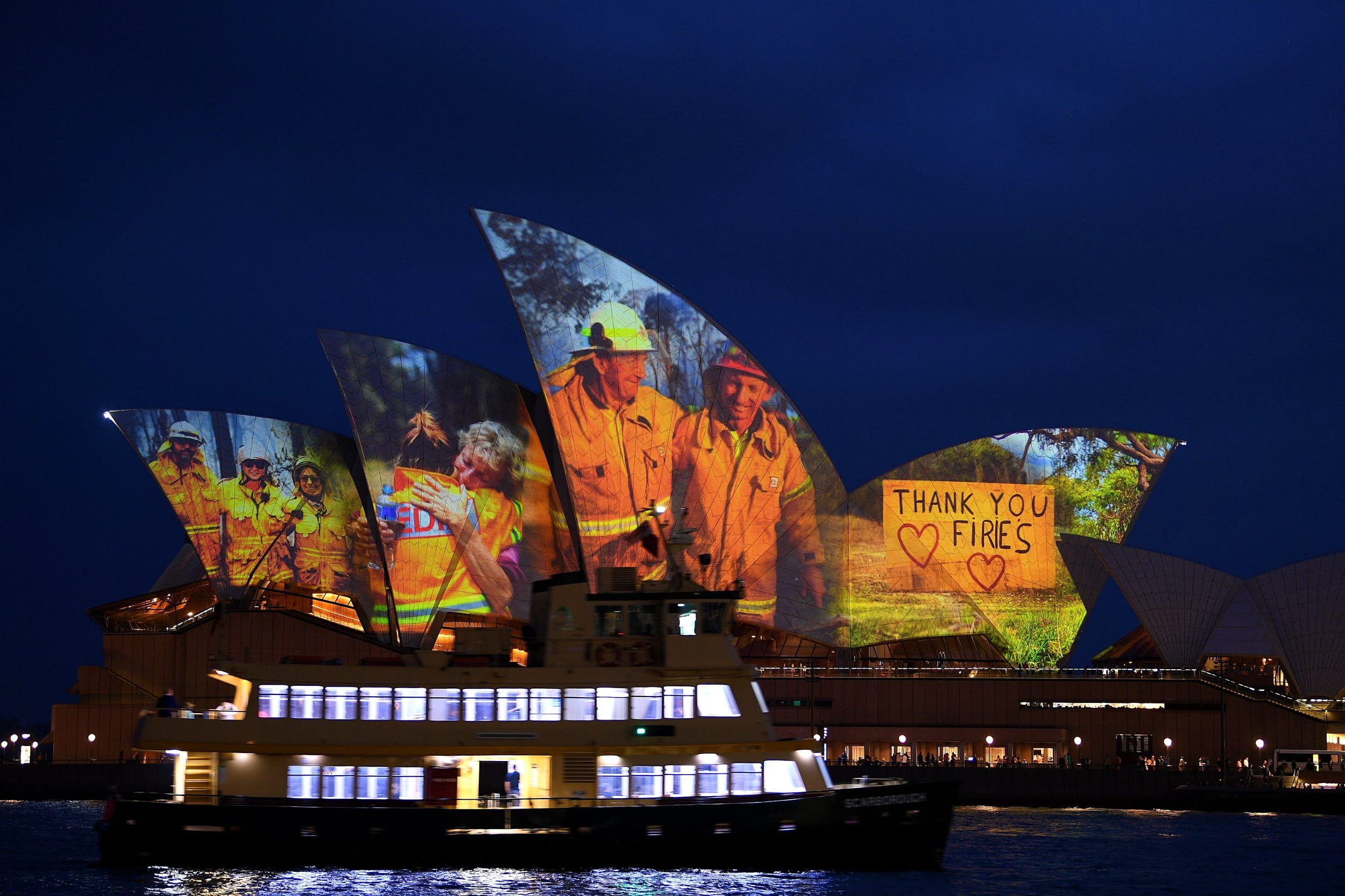 A cruise ship in front of the Sydney Opera House, which is lit up with a tribute to firefighters