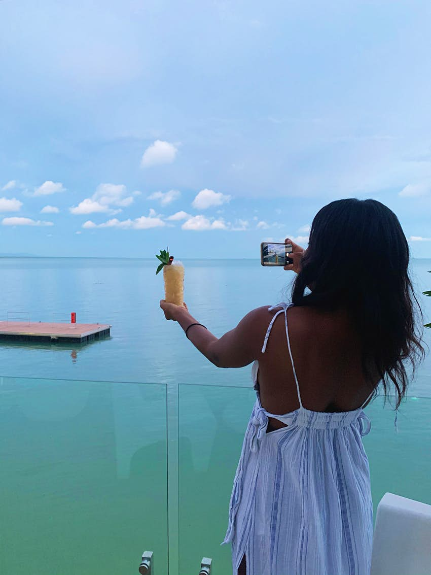 A woman holds up a drink with one hand while snapping a photo with her camera phone with her other hand.