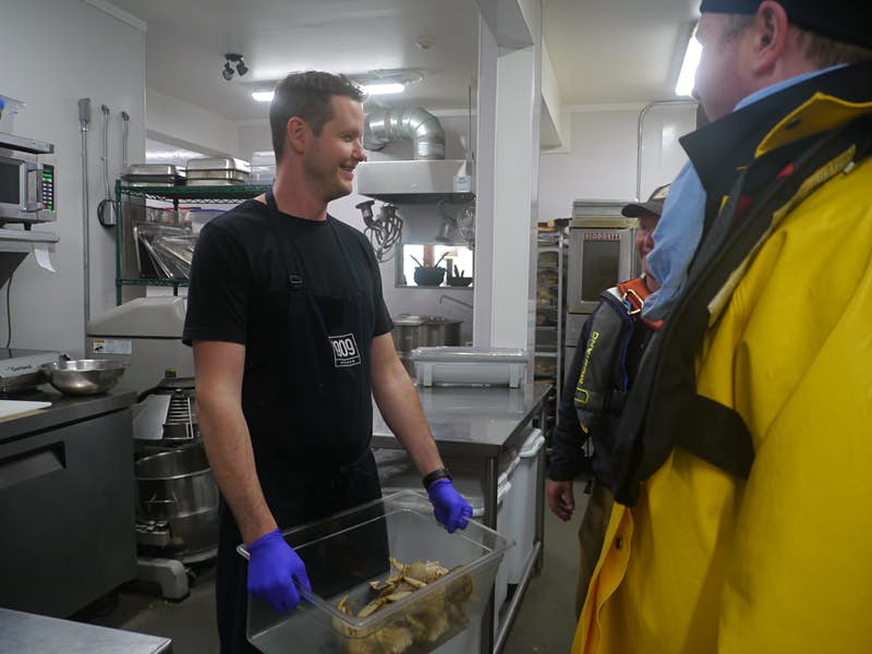 Chef Paul Moran stands back of house at 1909 Kitchen surrounded by stainless steel industrial cooking equipment and holding a plastic bin full of fresh crabs. He has blue plastic gloves on his hands and a big smile as he looks to the right side of the frame, where two fishermen are standing in yellow waterproof jackets.