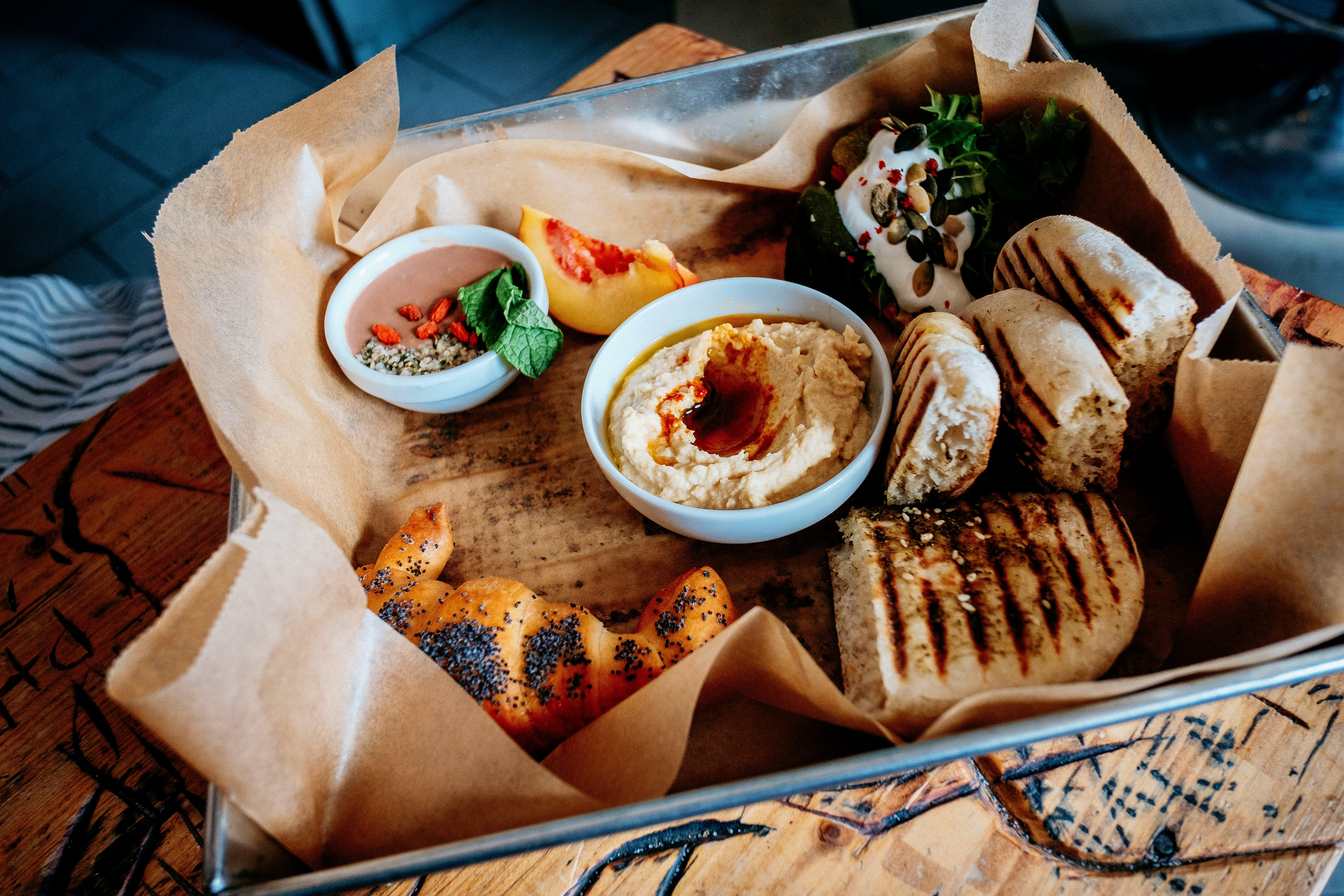 Chargrilled bread, hummus and other dips are arranged in a metal tray lined with baking parchment as part of the Taste of Prague Food Tour.