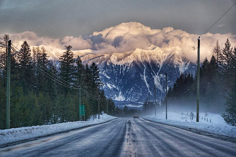 A vehicle is in the middle distance, driving along a snowy road lined with tall pine trees. Snow-laden, forested mountains are straight ahead, and huge clouds linger on top of them, under a grey sky.