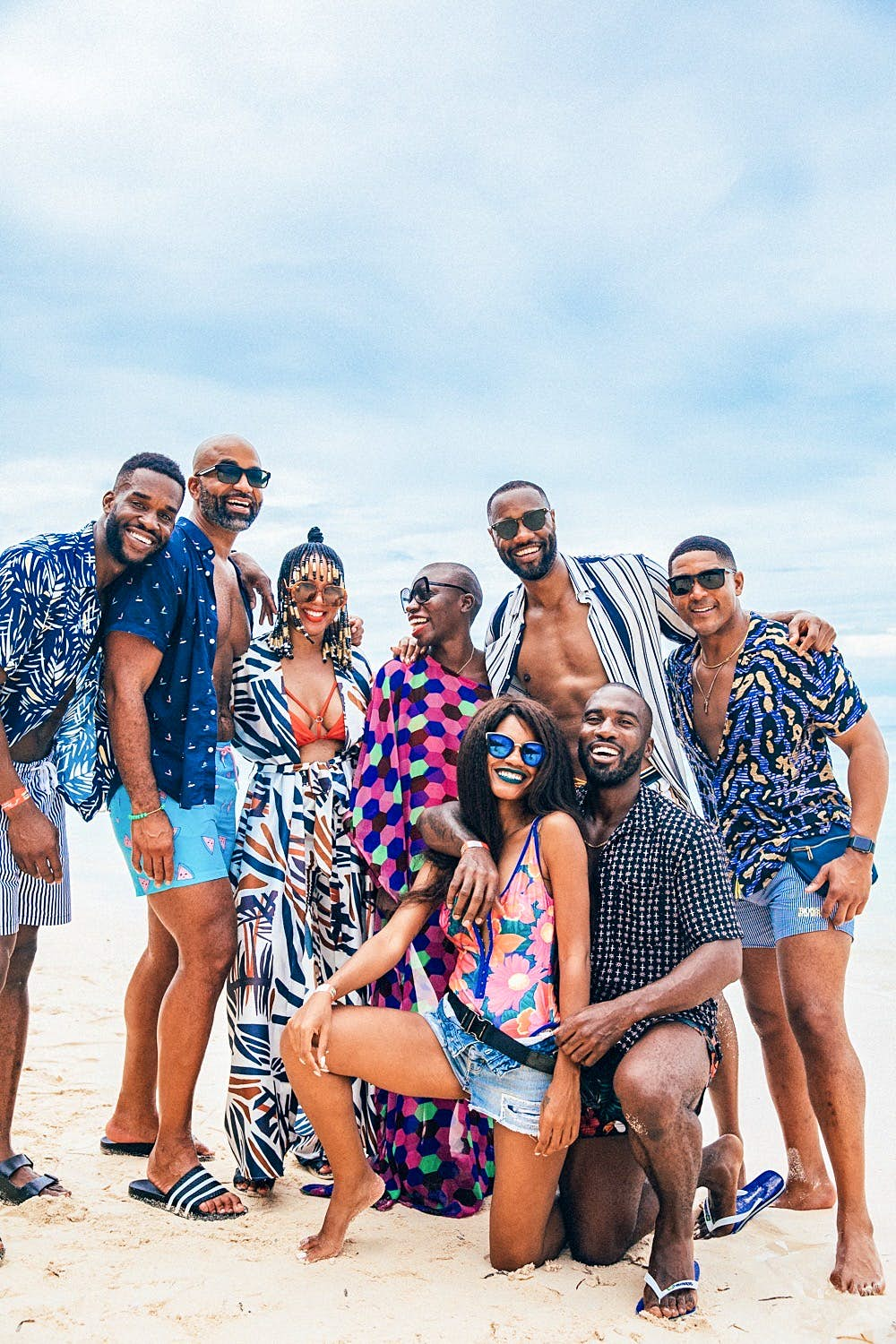 A group of people smiling and posing on the beach, in the Seychelles to celebrate Jessica Nabongo travelling to every country in the world