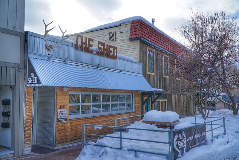 The exterior of a bar/restaurant, ; it has horizonal wood cladding and a corrugated metal awning decorated with a set of antlers and The Shed in red, cut-out letters. A few tables in an outdoor seating area are laden with several feet of snow.