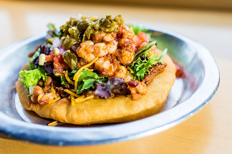 Closeup of a open-faced taco piled high with shredded meat, cheese, lettuce, tomatoes, corn and jalapenos; Indigenous food
