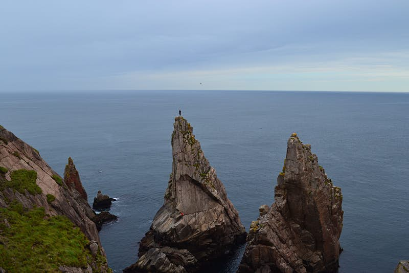 A person stands on the top of high, narrow piece of rock jutting directly up from the sea.
