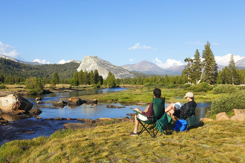 Two campers sit near a river in Yosemite National Park, California