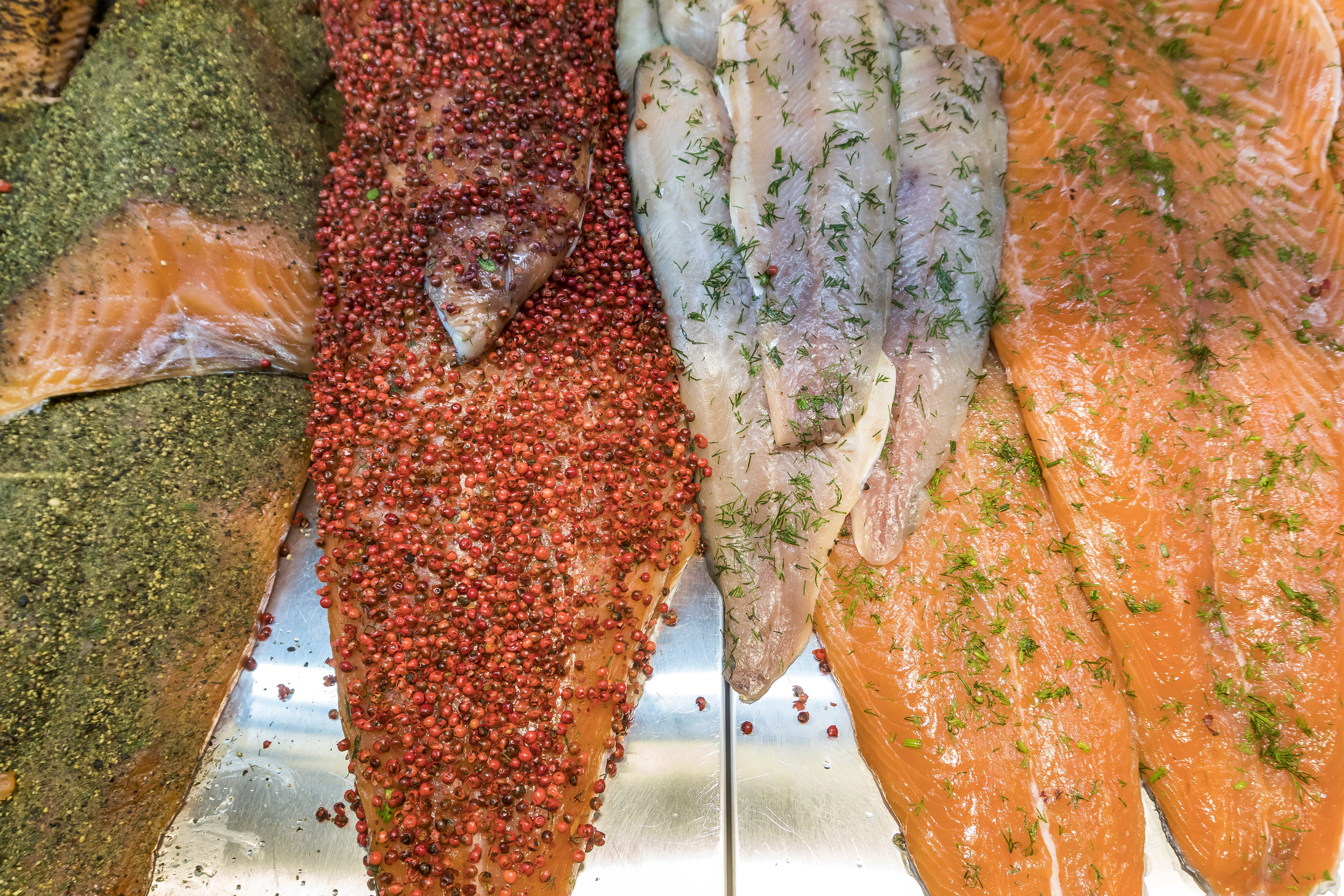 Several fillets of fish have been coated with different colorful herbs and spices at Vanha Kauppahalli in Helsinki.