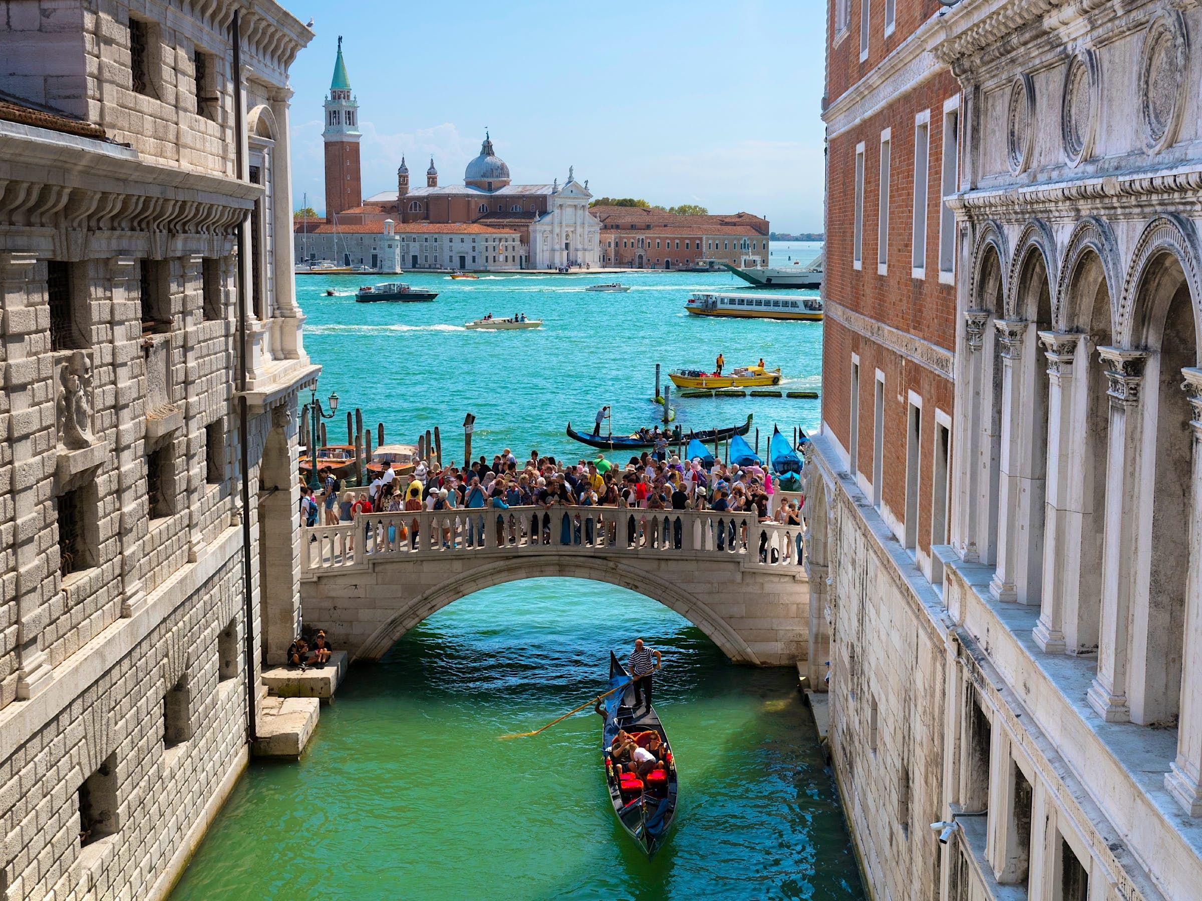 Uma gôndola viaja sob a ponte movimentada Ponte della Paglia, em Veneza.