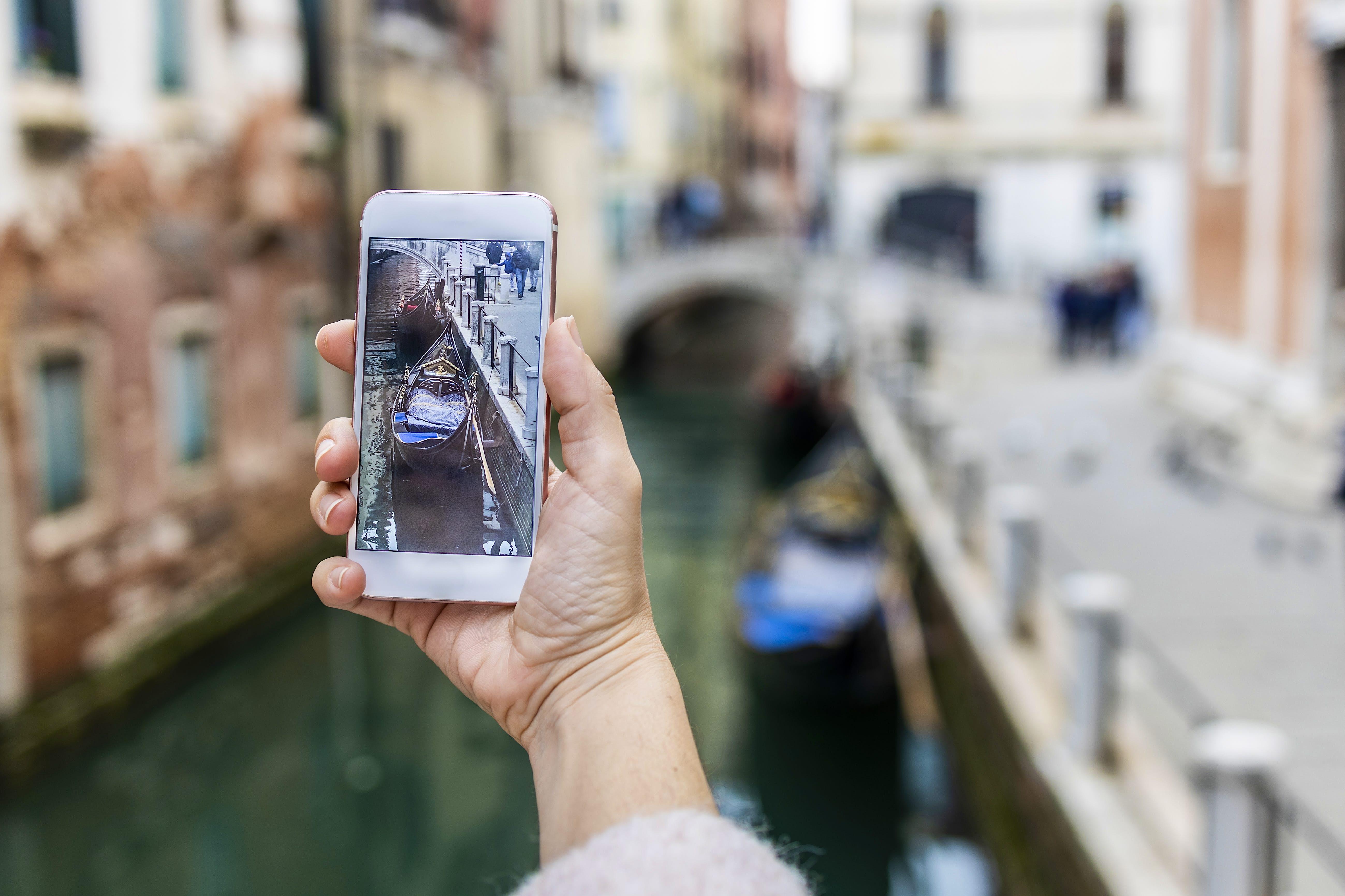 Mão cortada de mulher fotografando com telefone celular em Veneza