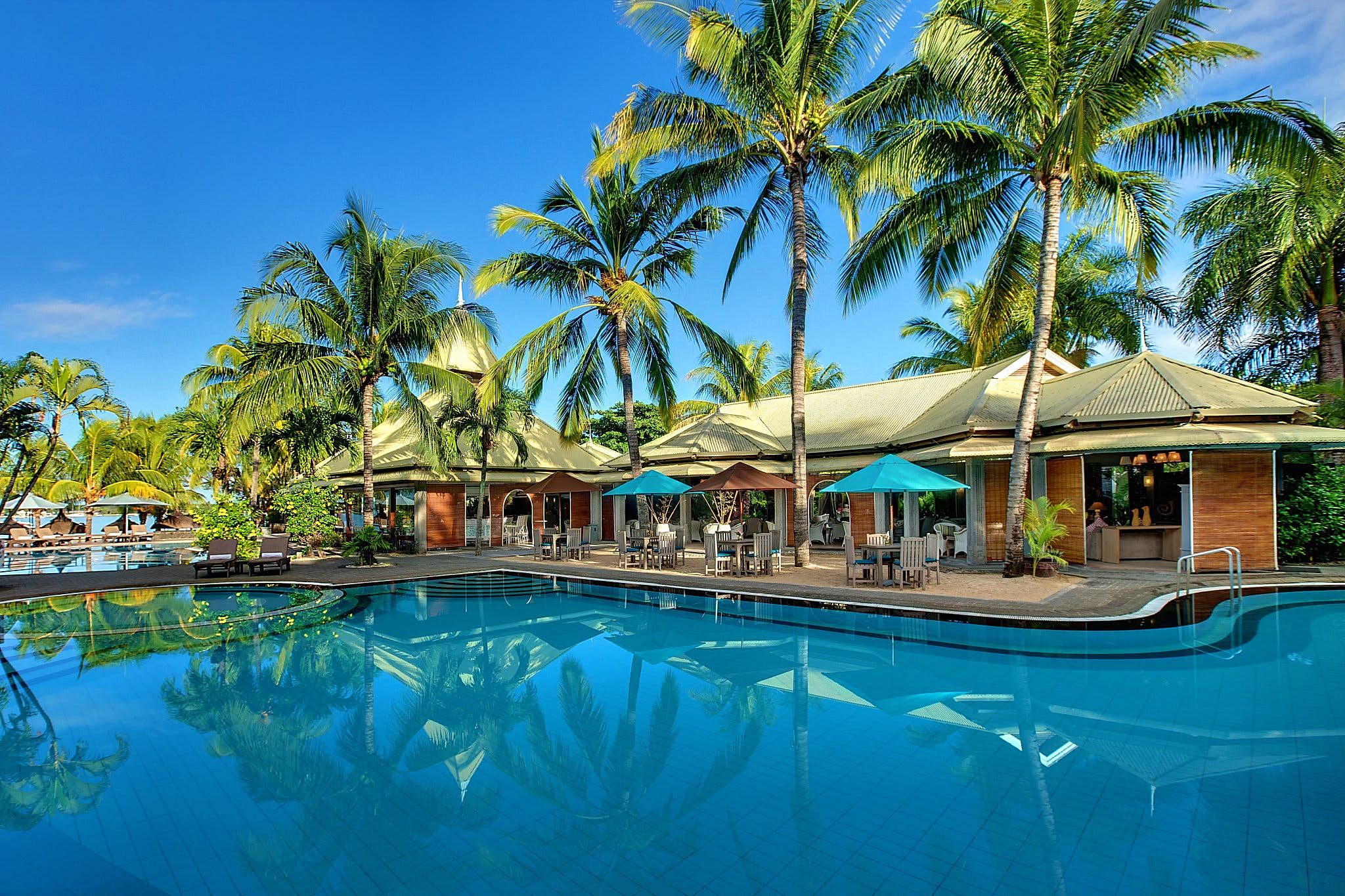 A swimming pool at the Veranda Grand Baie Mauritius, on a sunny day. Palm trees and awnings are visible poolside, along with chairs and parasols
