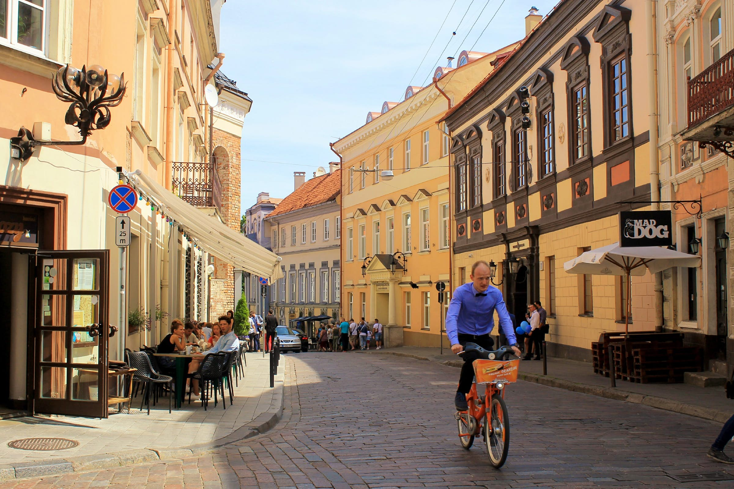 Un hombre monta su bicicleta por una calle en el casco antiguo de Vilna, mientras la gente se sienta en un café.