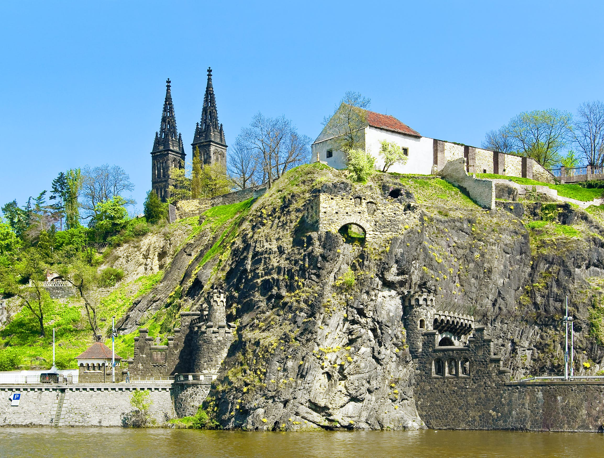 The Vyšehrad Citadel built on the Vltava River; rock ramparts flank the water's edge and rise up the slope to buildings and the twin-spired church.