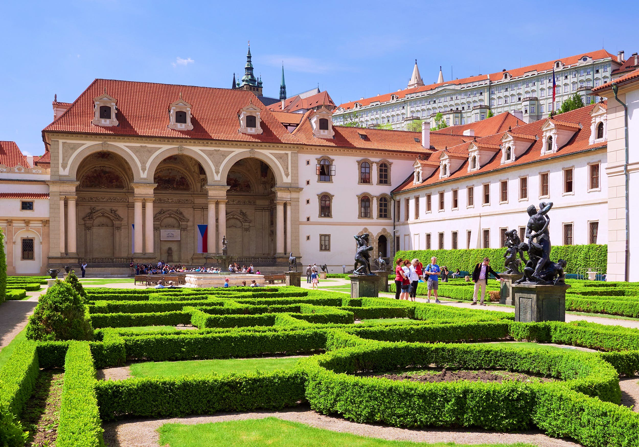 In the foreground is a manicured set of lawns and hedges that break up the garden into various geometric shapes; the garden is backed by a historical Wallenstein Palace