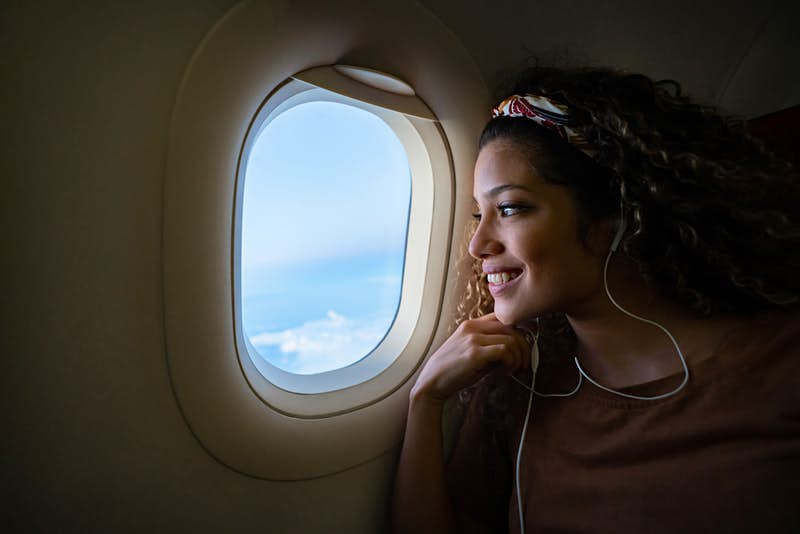 A young woman looks out an airplane window at the clouds; frequent fliers' final call secrets