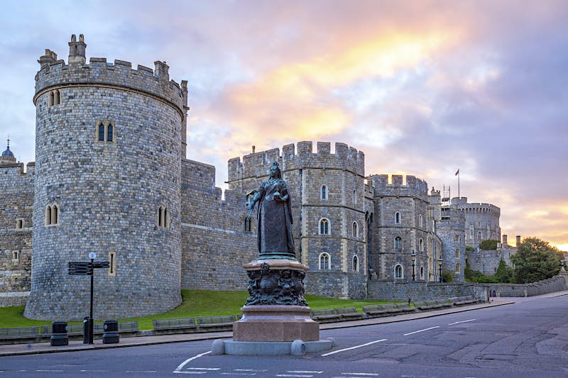 A statue of Queen Victoria in the middle of a road next to Windsor Castle at sunrise; Heathrow Layover