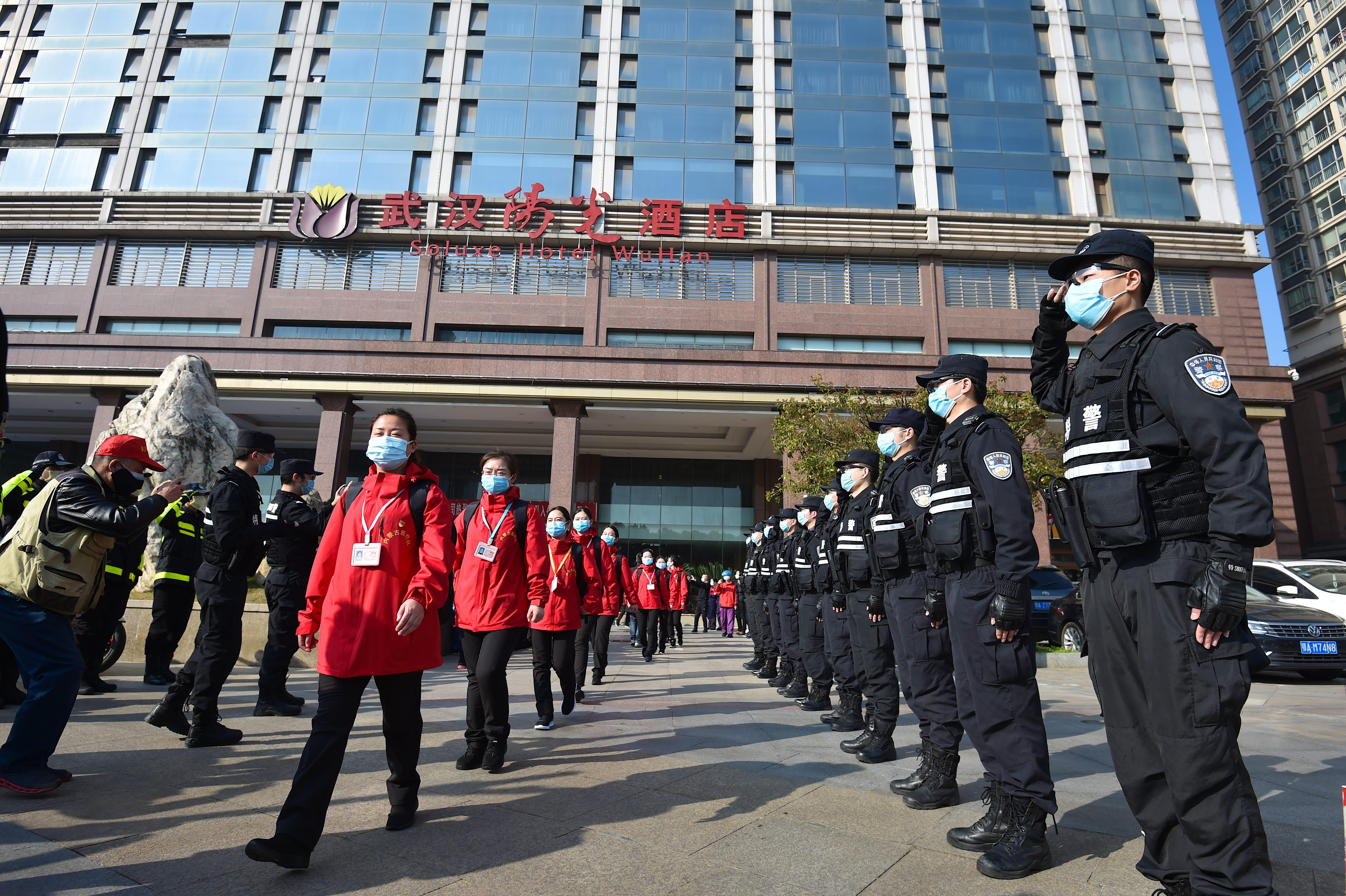 A polícia chinesa está saudando a equipe médica enquanto saem de seu hotel durante a pandemia de coronavírus