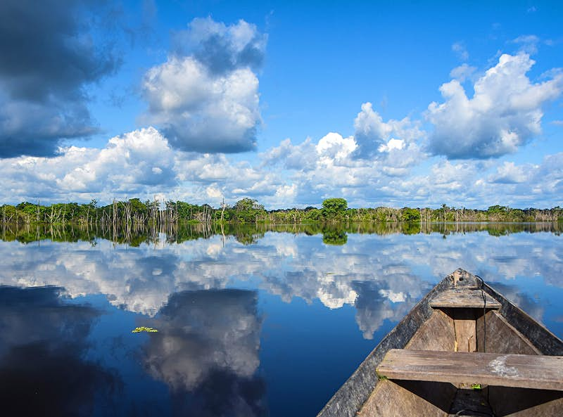 A view of the still water of Xixuau from a wooden canoe.