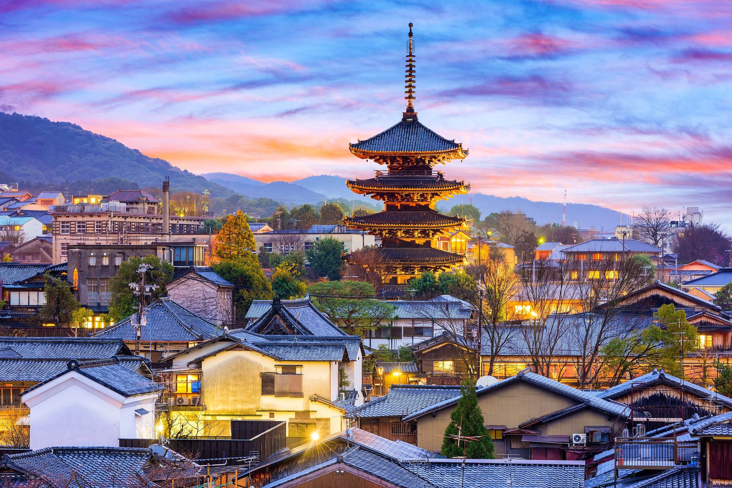 Rooftops and a towering shrine rising into the sky at sunset within Higashiyama