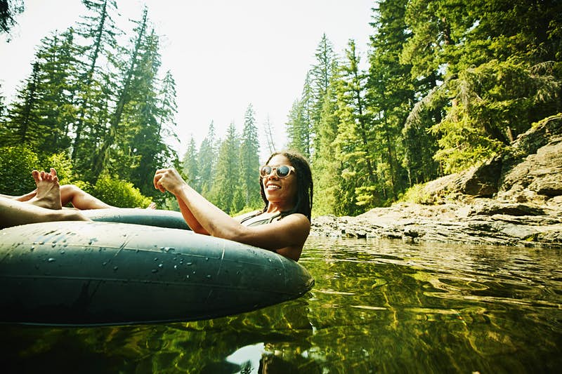 A smiling woman with sunglasses floating down a river on an inner tube on a sunny day.
