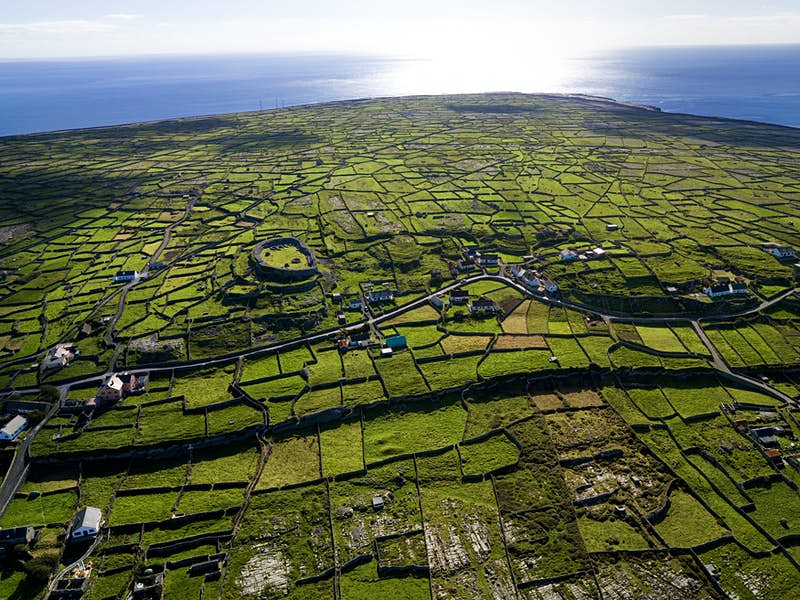An aerial view of the island on a sunny day, including a prehistoric stone fort, green fields and stone walls