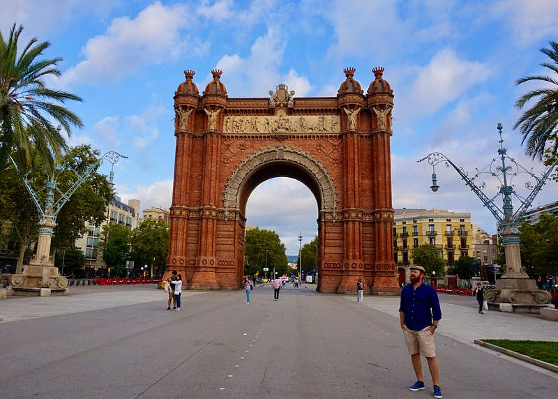 Writer Daniel poses in front of Barcelona's Arc de Triomf, a huge freestanding red-brick arch; he wears beige shorts, a blue shirt and a flat cap.