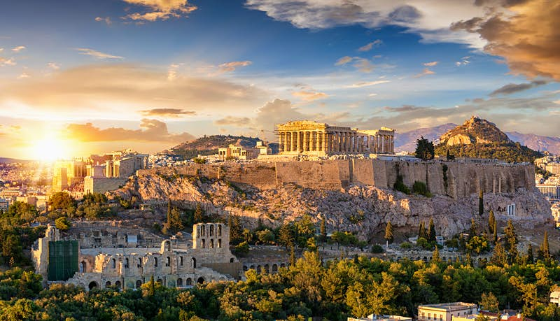A skyline of Athens bathed in golden light.