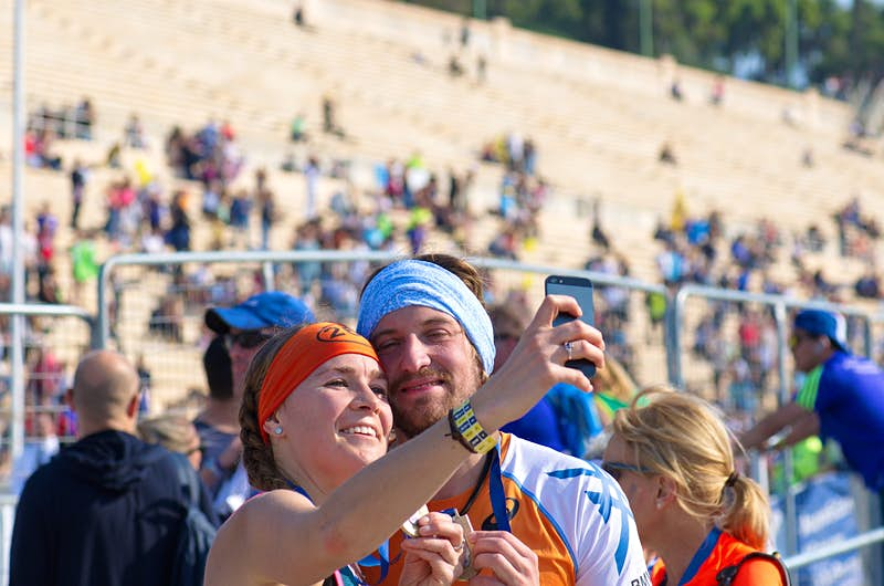 Happy couple taking a selfie after finishing the 33rd Athens Classic Marathon; in the background are the stone stands of the Panathenaic stadium or kallimarmaro (site of the first modern Olympiad in 1896)