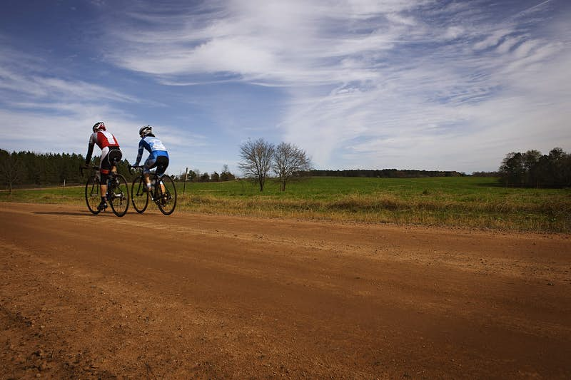 Two cyclists pedal along a red-coloured dirt road in the countryside.