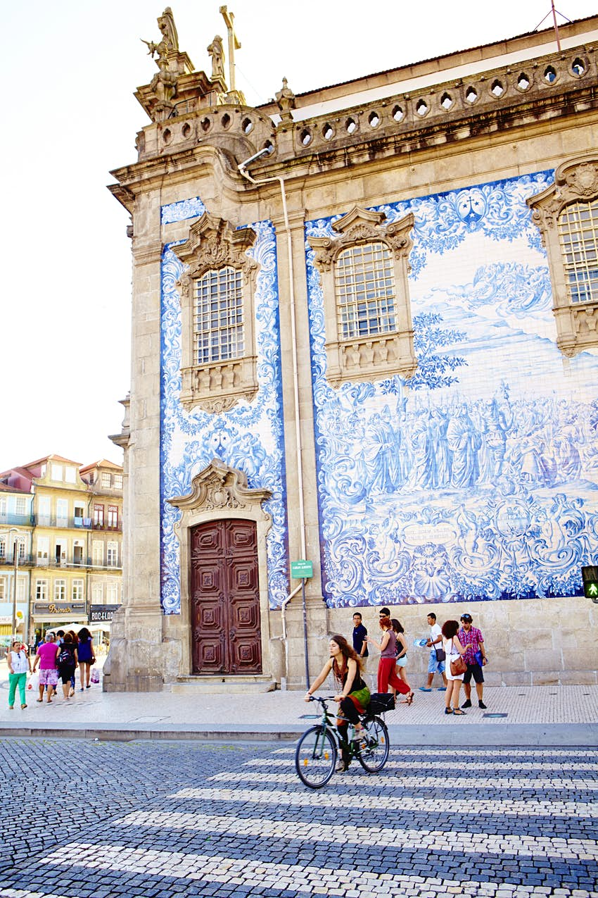 Igreja do Carmo church decorated with azulejos (painted ceramic tiles); the street outside has a zebra crossing and a woman on a bike is cycling on it.