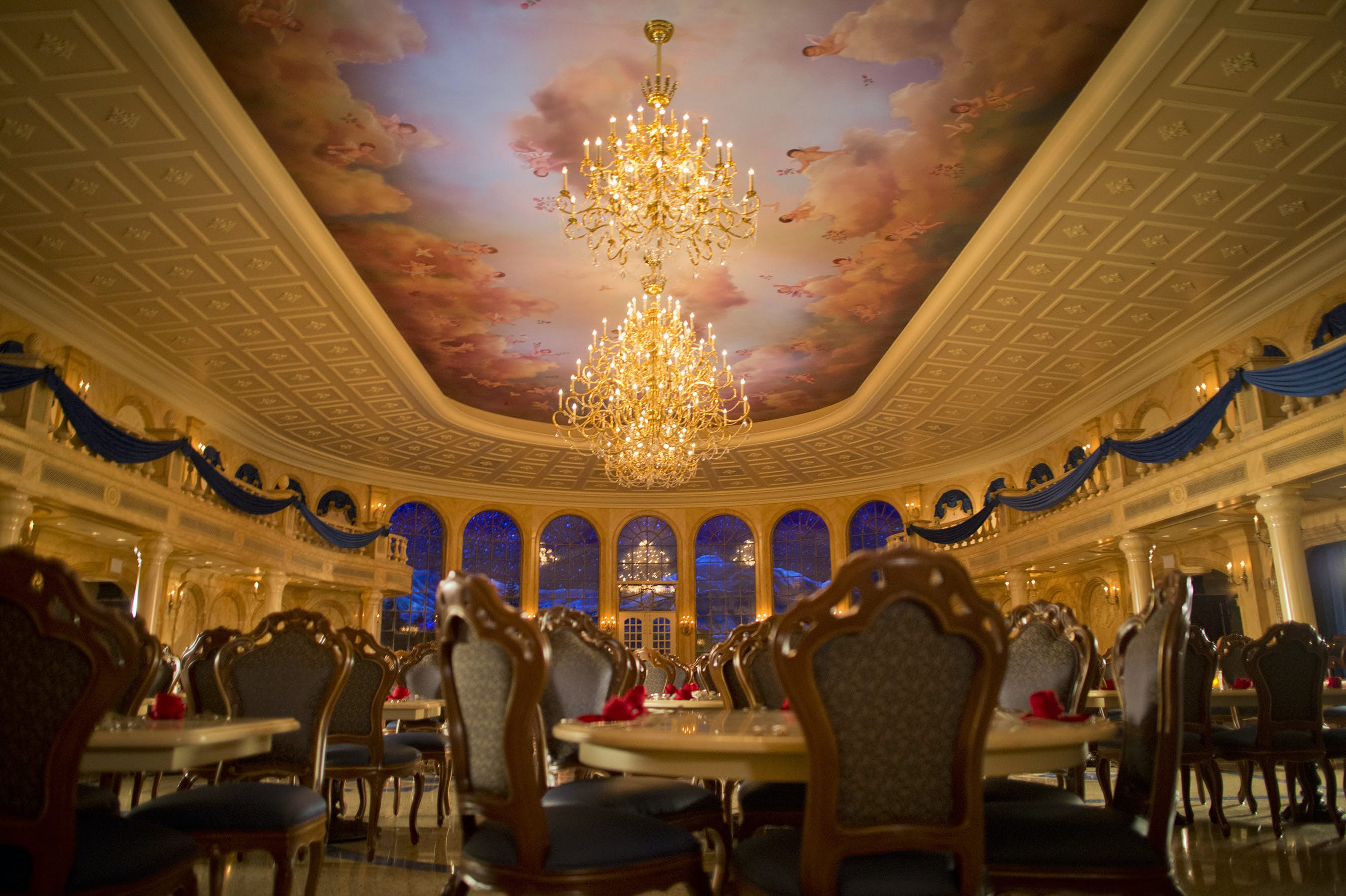 A replica of the ballroom from Disney's Beauty and the Beast, including high ceiling with clouds and cherubs painted on it and a sparkling chandelier