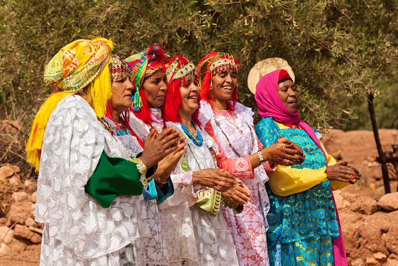 Six Berber women stand in a line at a wedding ceremony, dressed in colourful clothing