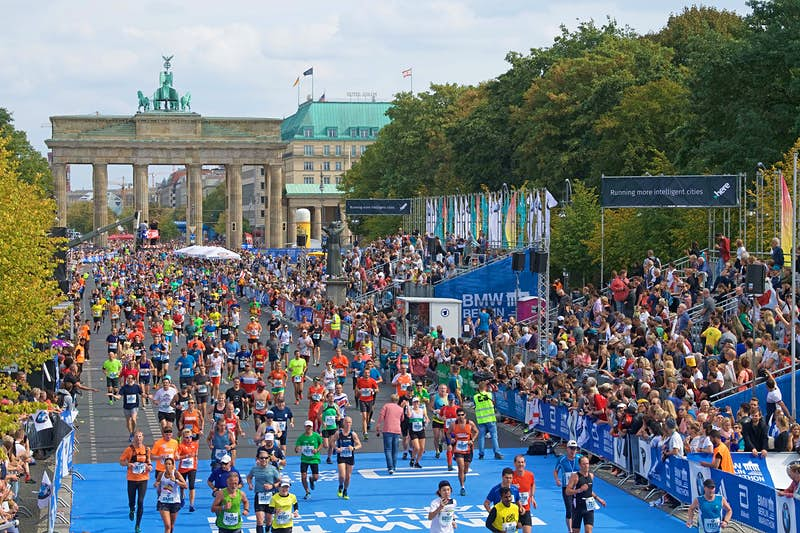 Thousands of runners stream through the Brandenburg Gate and run towards the camera down a tree-lined boulevard.