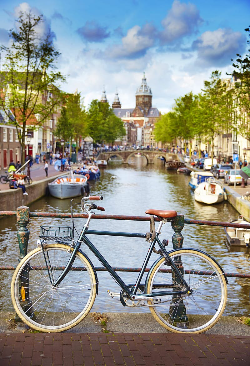 A traditional bicycle is parked against a hand rail on a bridge over one of Amsterdam's canals; boats line the canal and a large church rises from its end in the distance.