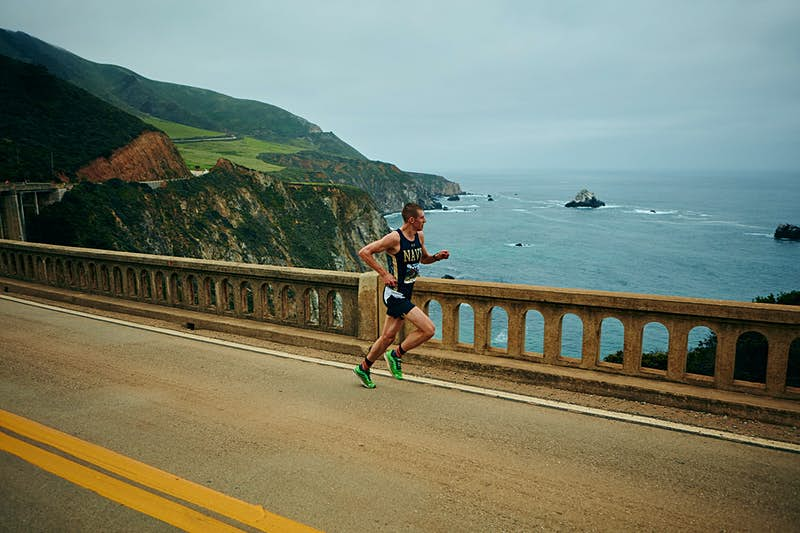 A lone runner heads along the coastal highway in the Big Sur International Marathon; beyond the stone railing the road drops off to cliffs and the Pacific Ocean
