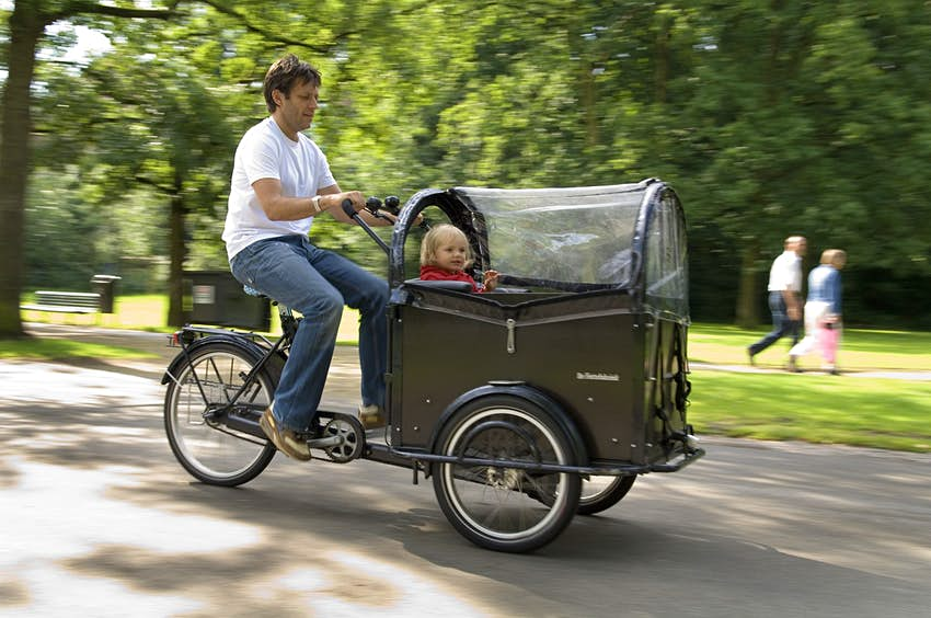 A man cycles an adult-size tricycle with a carriage at the front of it through a park. A small child is sat in the carriage