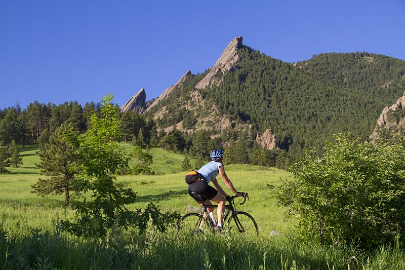 A lone cyclist pedals through rolling hills covered in grass and forest; she looks up to some rocky peaks above.