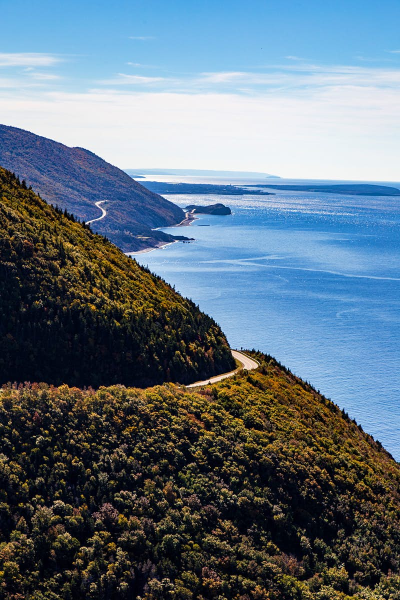 This image looks along a coastline, which has two forested promontories sticking out into the ocean; cut into both is the snaking Cabot Trail.