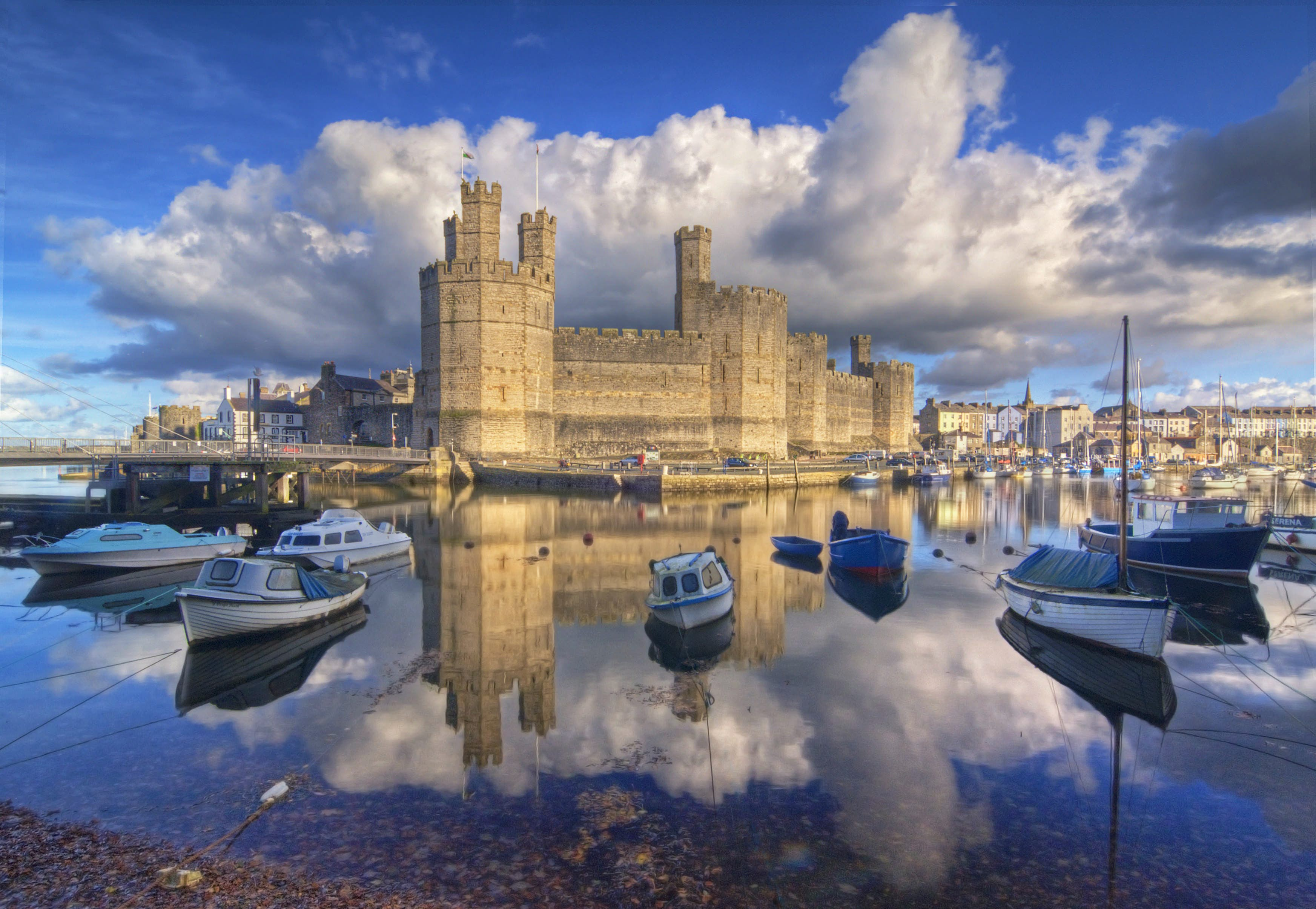 Several small boats sit on the glassy water surrounding Caernarfon Castle in Wales; picturesque waterfront buildings can be seen in the background.