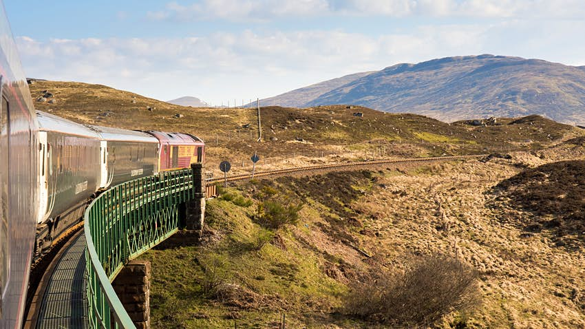 The Caledonian Sleeper train crosses Rannoch Viaduct on the scenic West Highland Line railway in the Scottish Highlands; the image is taken from the train on a curve, so you see the train arching ahead through a barren looking section of rolling hills..