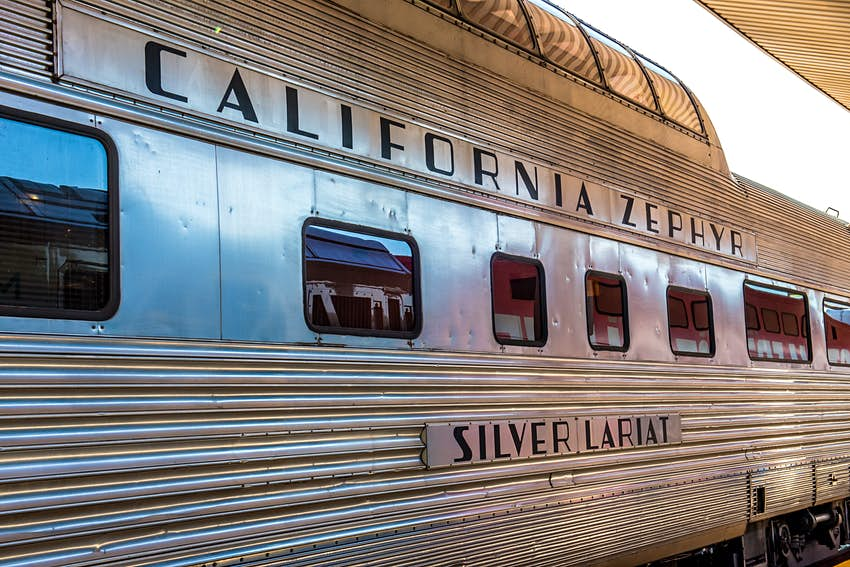 A silver train car with a glass rooftop viewing area sits at a station platform; emblazoned on the side is California Zephyr and Silver Lariat.