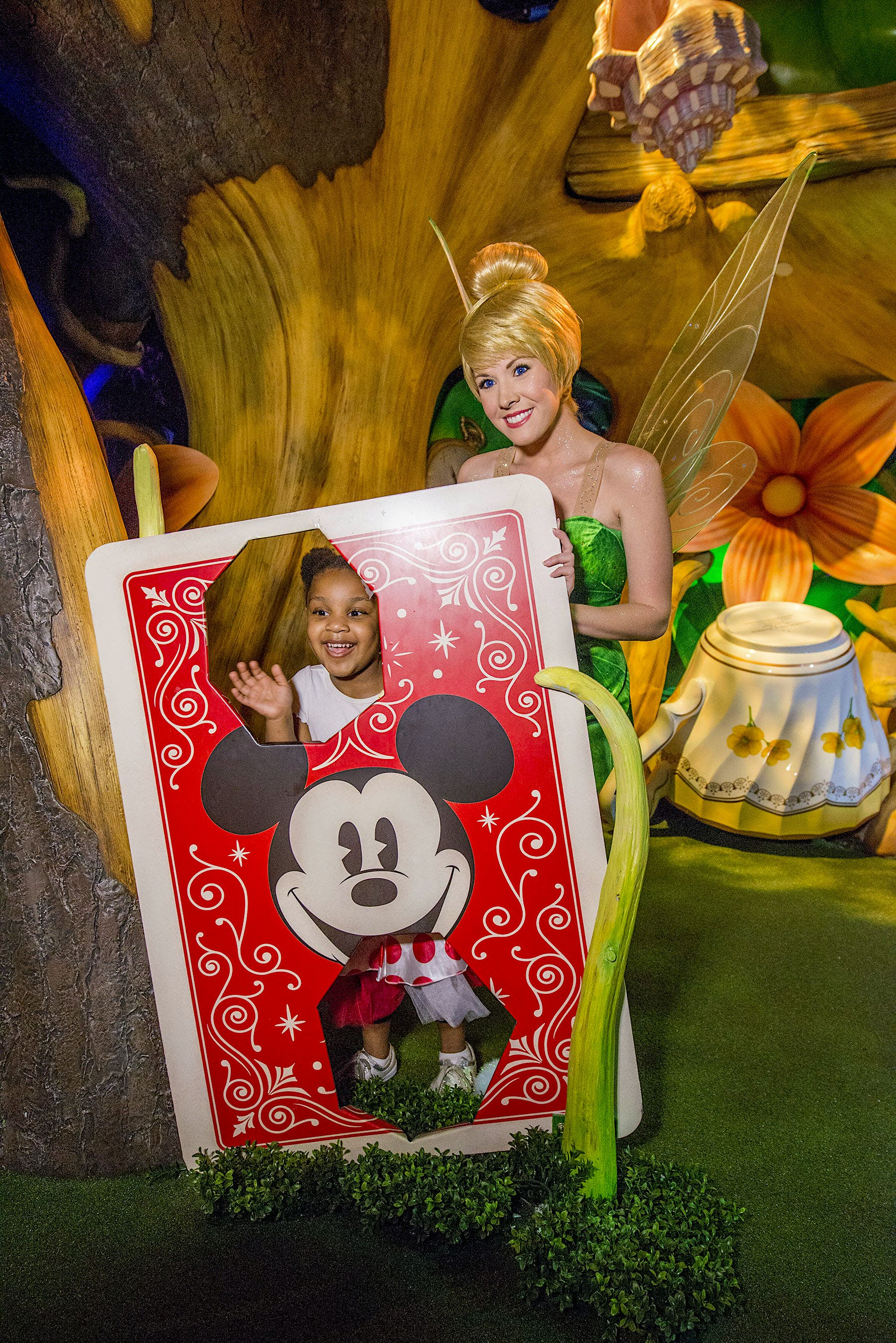 Tinker Bell strikes a pose with a young girl behind a large Mickey Mouse playing card