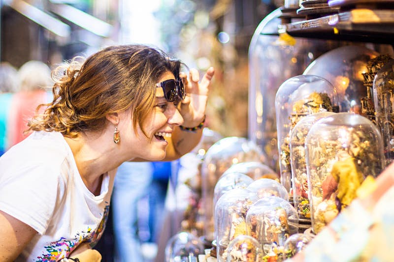Smiling woman looking at glass-domed items at a street market in Naples.