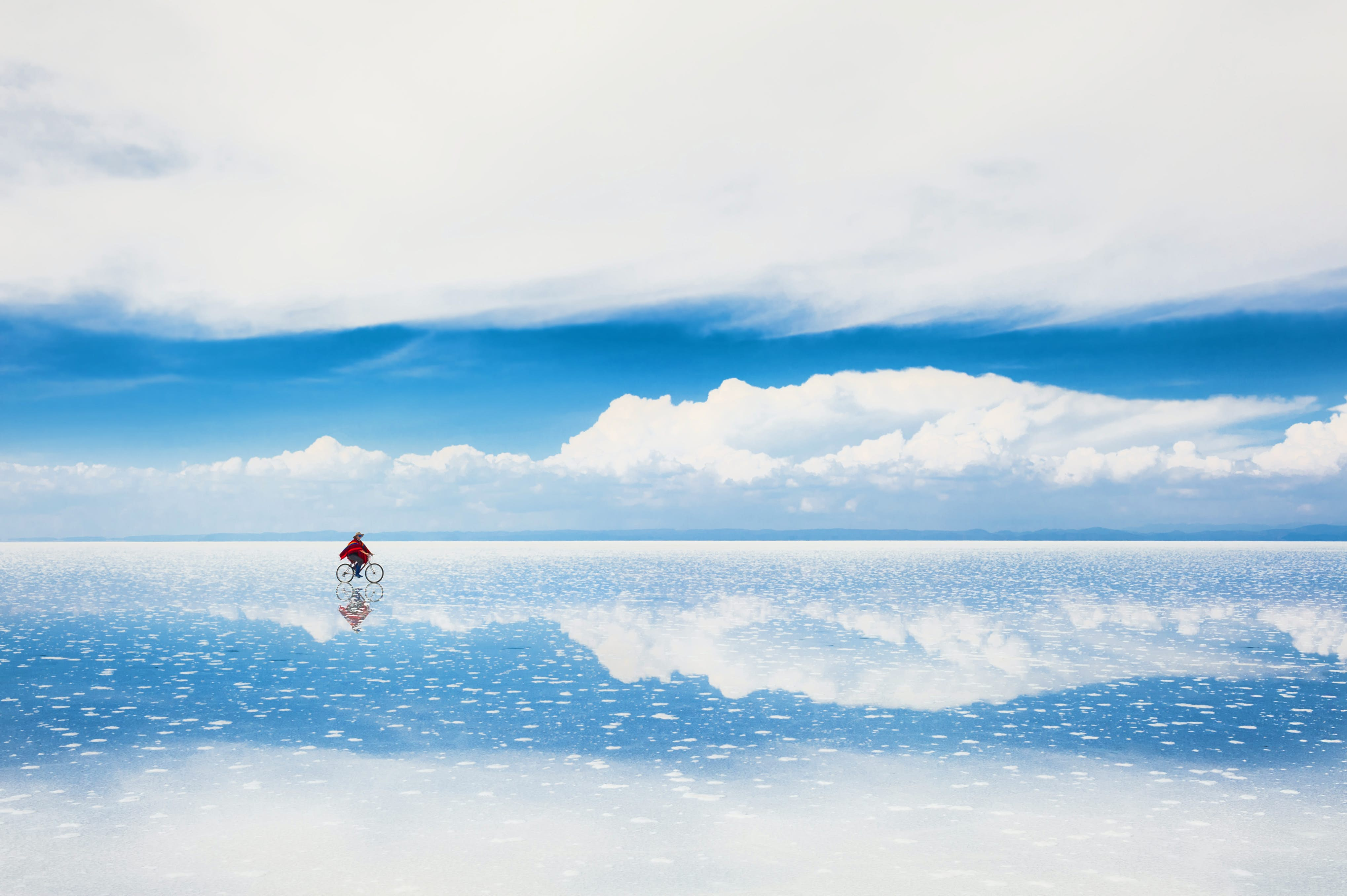 A lone cyclist rides across the Salar De Uyuni salt flats in Bolivia. The rider's image, and the blue sky above him, is reflected in the white, salty ground.