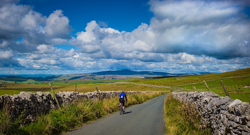 A lone cyclist pedals along a narrow stretch of road lined by old stone walls; the road meanders into the distant hills.