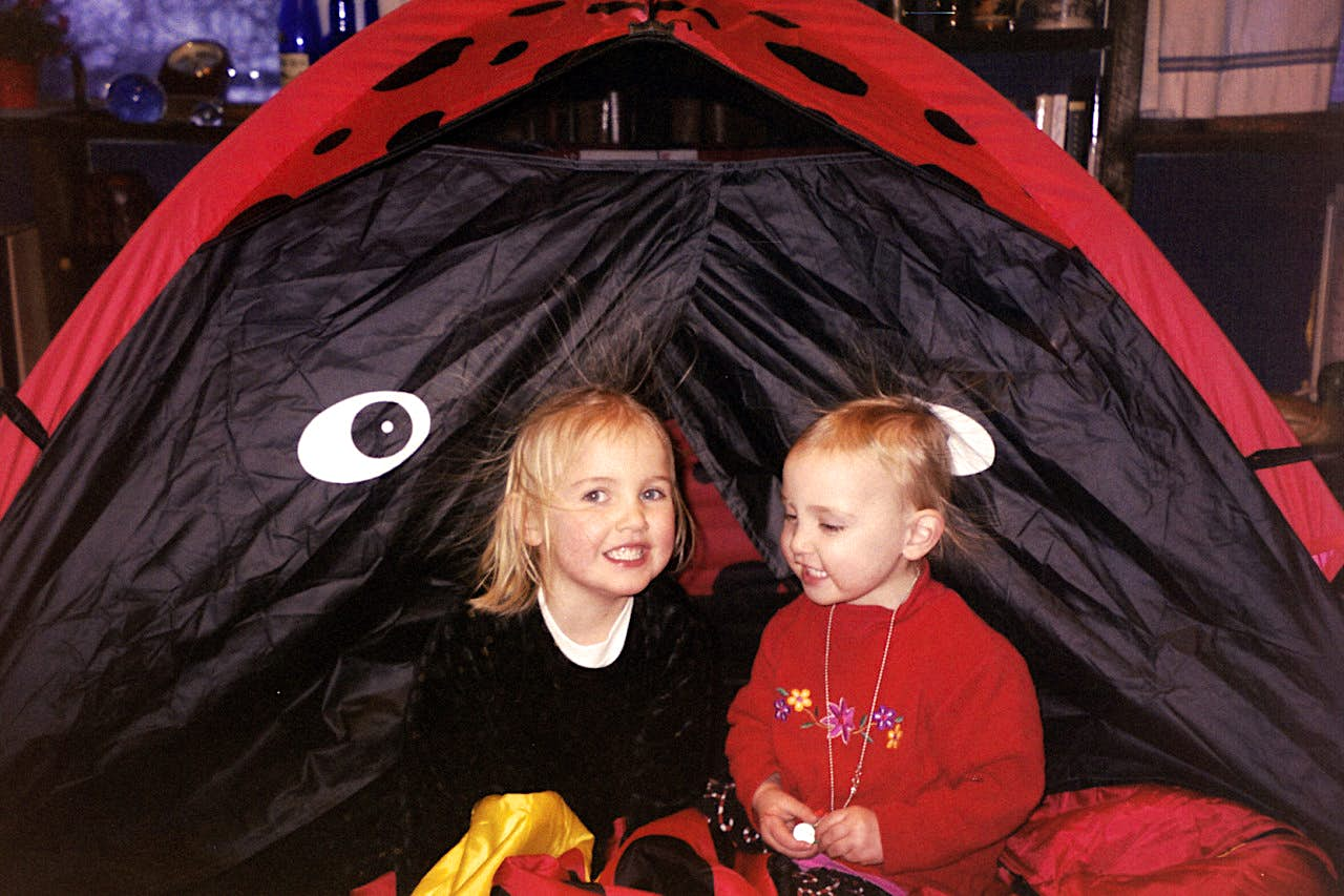 Two young girls play in a tent made to look like a ladybug, as their hair stands on end from the static; kids outdoor adventures