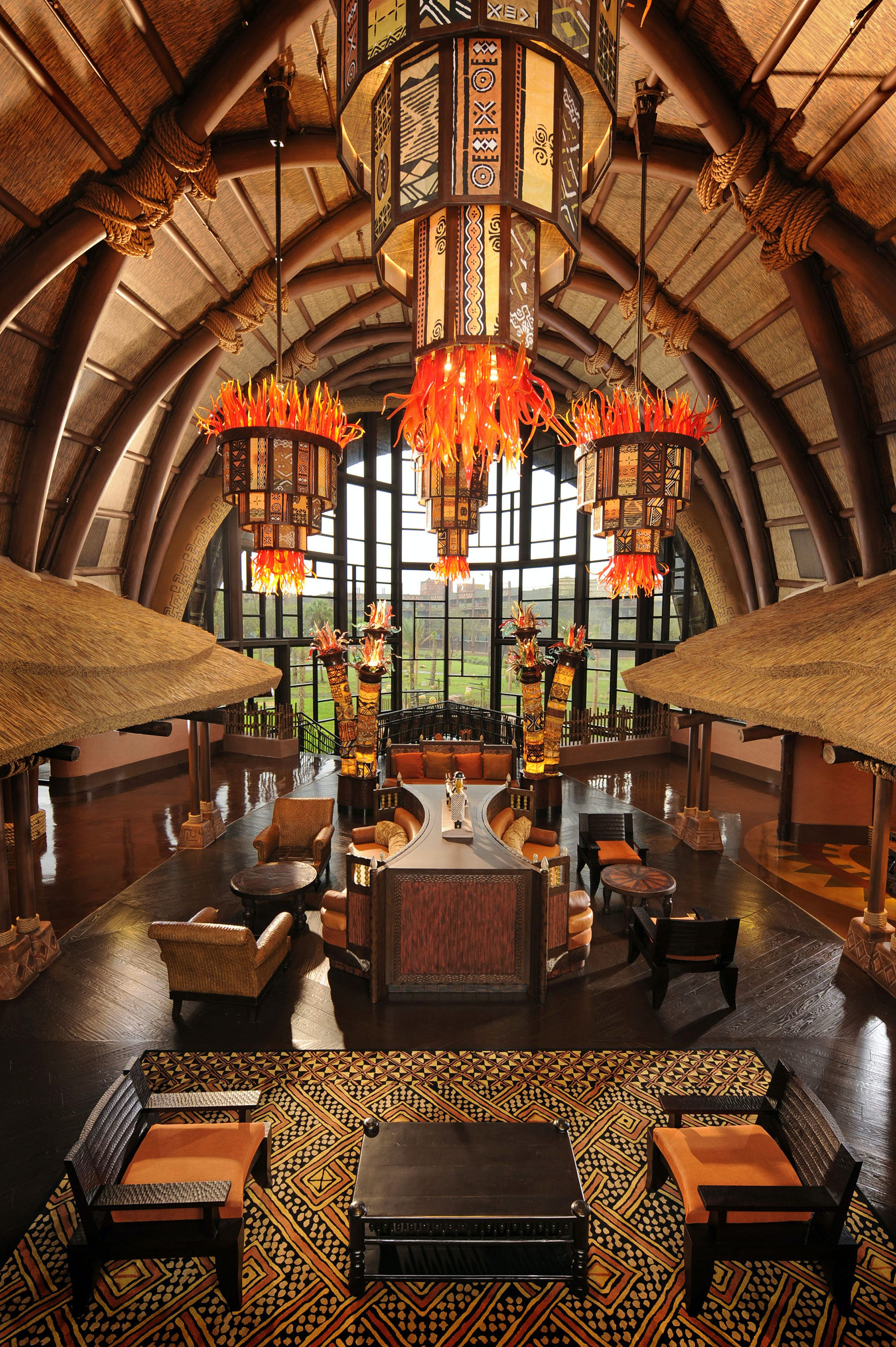 A hotel lobby with arching windows, Africa-inspired art, floor lamps and hand-carved wooden columns