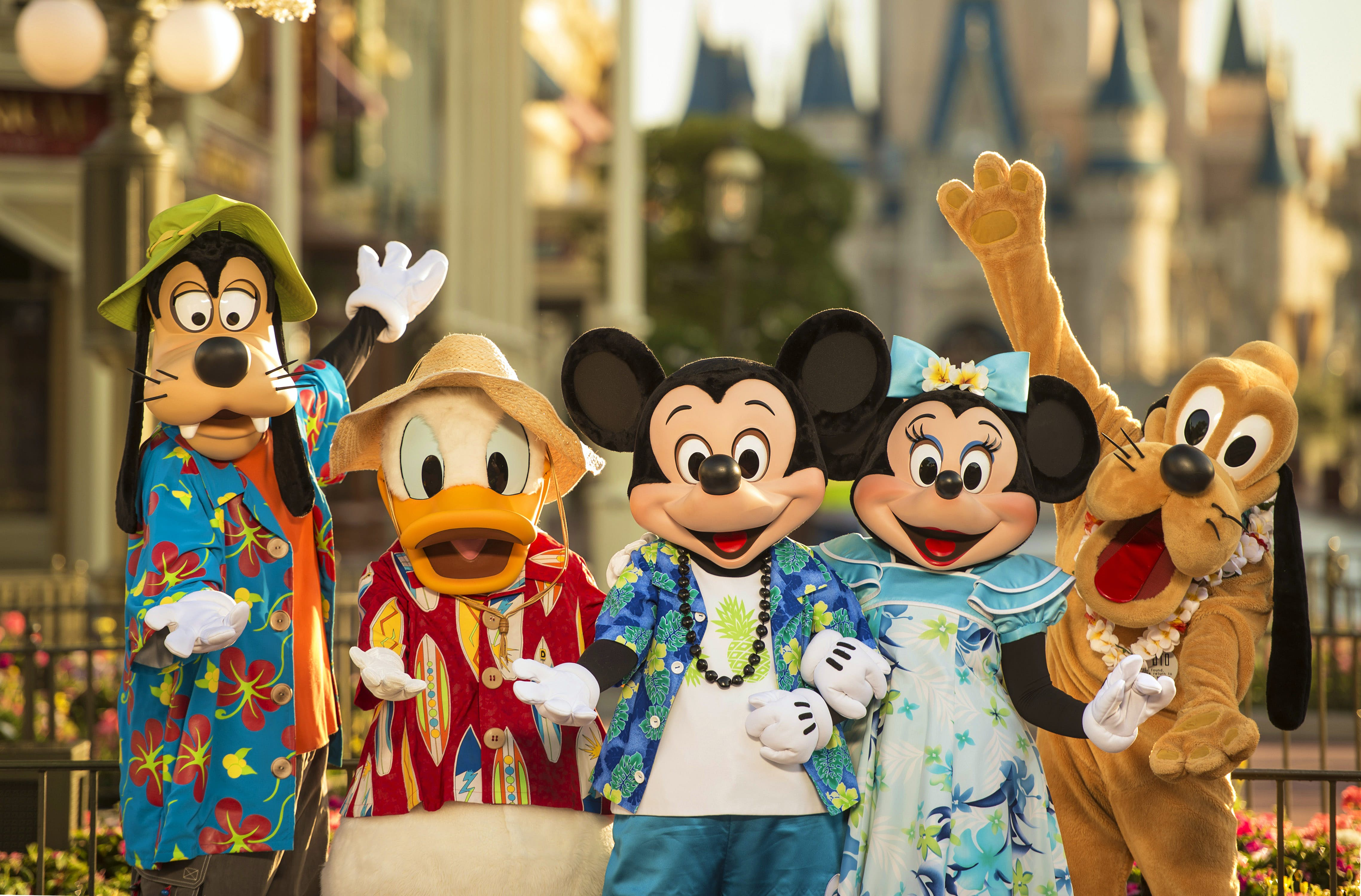 Goofy, Donald Duck, Mickey and Minnie Mouse and Pluto all pose hands outstretched in Hawaiian print clothing